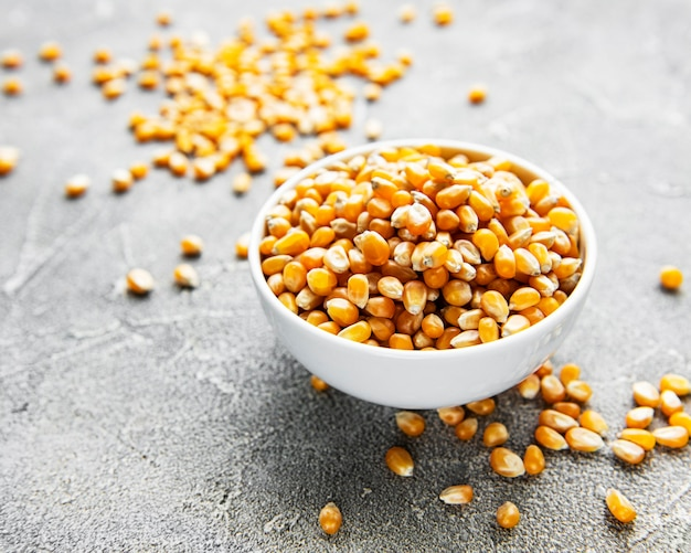 Dry corn seeds in white bowl on concrete background
