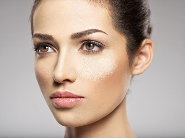 마른 화장품 메이크업 파우더가 여성 얼굴에 있습니다. 미용 치료 개념. 소녀는 메이크업을합니다.