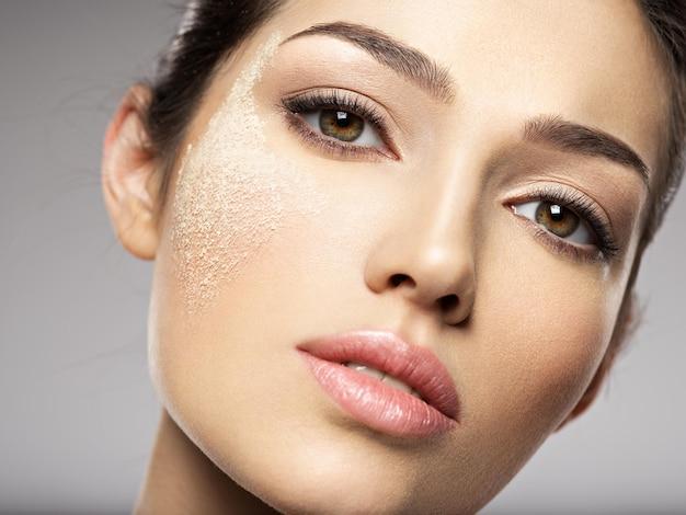 ドライコスメティックメイクアップパウダーが女性の顔にあります。美容トリートメントのコンセプト。女の子は化粧をします。