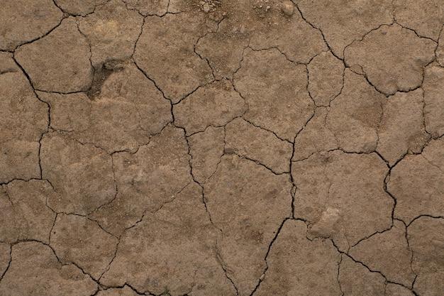Текстура сухой потрескавшейся земли коричневой. без полива пустыни.