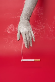 Dry and cracked hand and a smoking cigarette on red background.