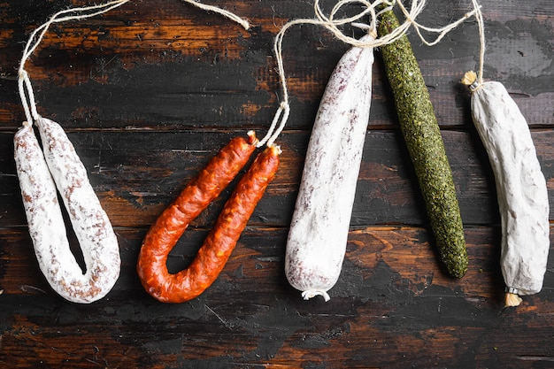 Dry cured fuet and other sausage s on wooden surface.