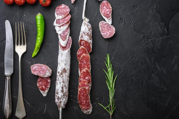 Dry cured fuet salami sausage slices  on black textured background with space for text.