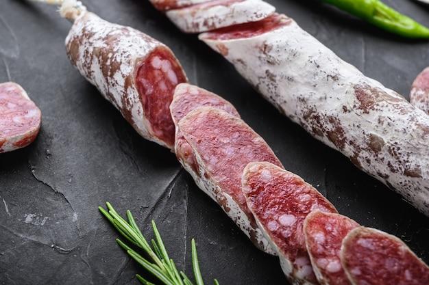 Сухие вылеченные кусочки колбасы салями fuet на черном текстурированном фоне.