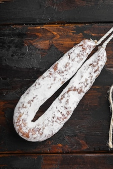 Dry cured fuet wurst on wooden surface.