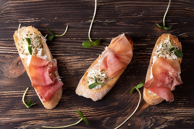 Dry cured ham crostini, toast with prosciutto ricotta and microgreens, rustic style.