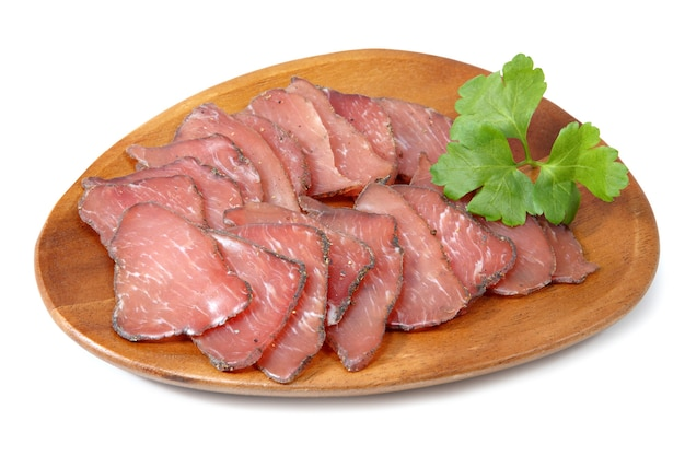 Dry-cured pork slices on wooden plate, isolated on white background.