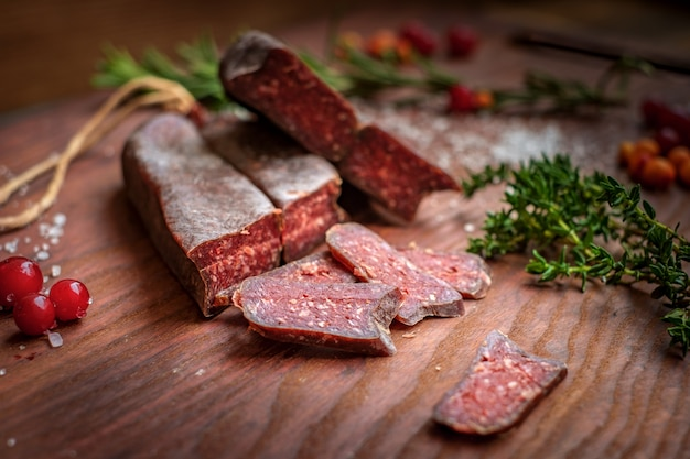 Dry-cured salami sliced on wooden background with grapes and herbs
