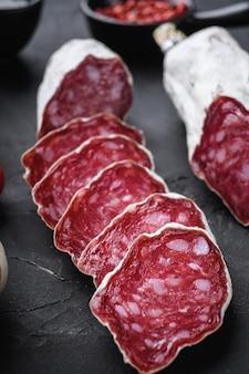 Сухие вылеченные ломтики колбасы сальчичон с травами на черном текстурированном фоне.