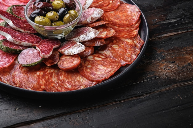 Dry cured sausage sliced chorizo, fuet, salami on wooden table.