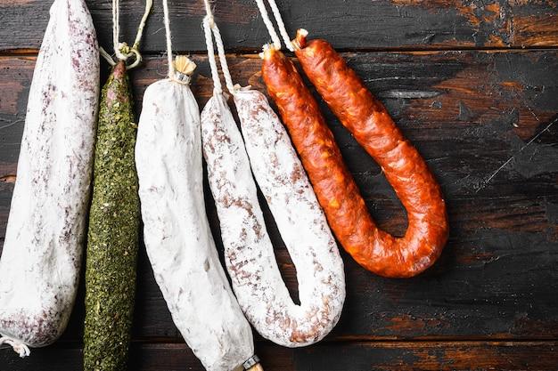 Сухие вылеченные испанские мясные колбаски, висящие на деревянной поверхности.