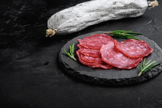 Сухие вылеченные, целые и ломтики колбасы сальчичон на черном фоне с копией пространства.