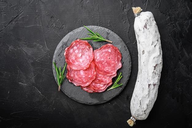 Вяленые, целые и ломтики колбасы сальчичон на черной текстурированной поверхности, вид сверху с местом для текста