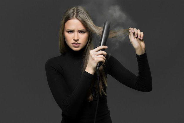 Dry damaged hair burned with hair iron concept. young girl holding hair iron burning her hair.