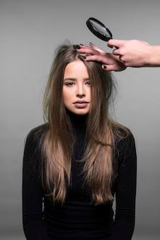 ダメージを受けた髪、フケ、髪、頭皮のケアのコンセプトを乾燥させます。彼女の髪をチェックしている若い女の子、拡大鏡を持っている手。