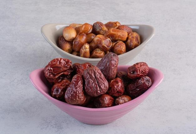 Сушеные финики и ягоды мармелада в керамических мисках.