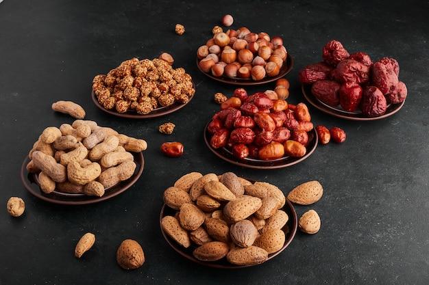 Сухие финики и орехи в блюдце на черной поверхности.