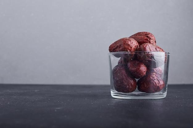 Datteri secchi in una tazza di vetro sulla superficie grigia.