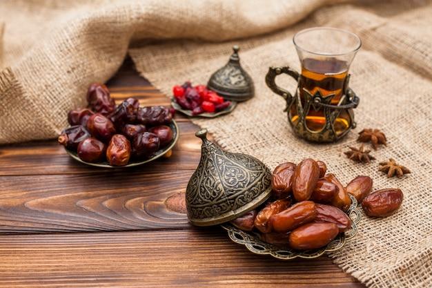 Dry dates and kumquats on saucers near cup of tea between burlap material