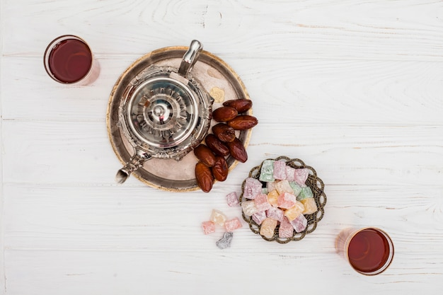 Dry dates near teapot, cups of tea and turkish delights