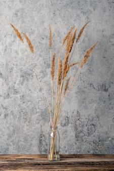 Сухие декоративные травы в прозрачной вазе.