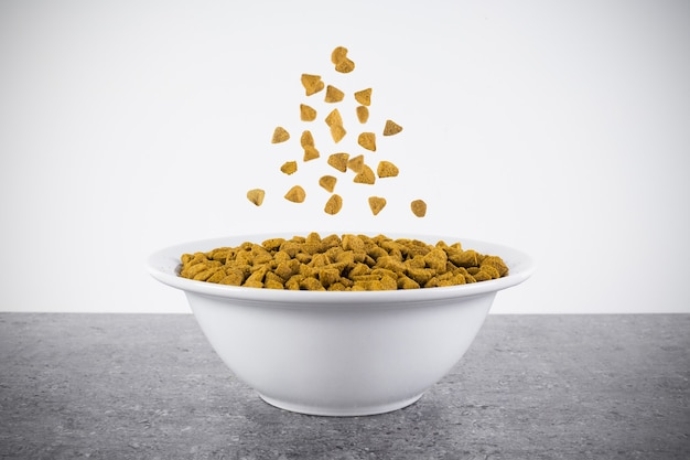 Dry dog or cat food in white bowl with pellets flying over it on gray granite surface