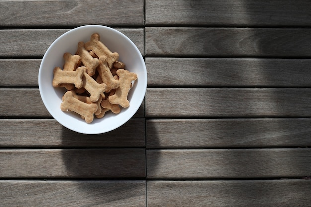 Dry dog food in a bowl on wooden background top view.
