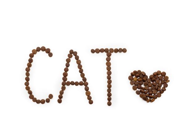ハートの形をしたドライドッグフードと白い背景の上の文字cat猫と犬のための食べ物