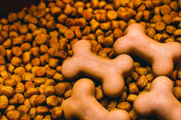 Dry dog food in small pieces and shaped like a bone