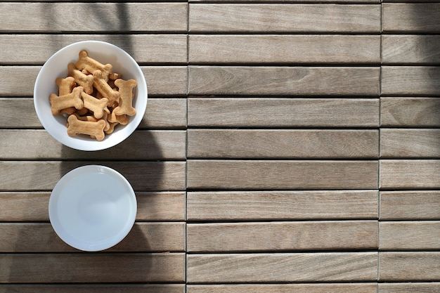 Dry dog food and water in bowl on wooden background top view.