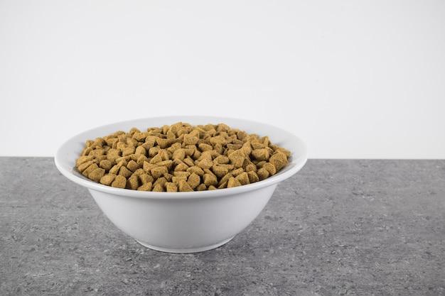 Сухой корм для собак или кошек в белой миске на серой гранитной поверхности