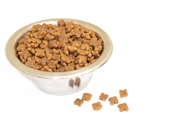 Dry domestic animal food in a bowl, isolated on white background