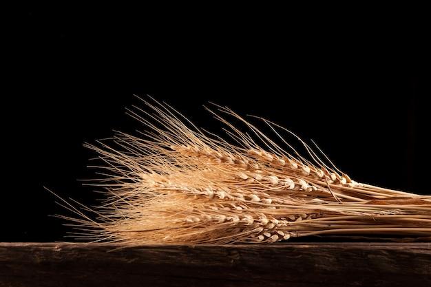 Сухие колосья пшеницы или ржи лежат на краю старого деревянного стола. естественный золотистый цвет растения. деревенский стиль,