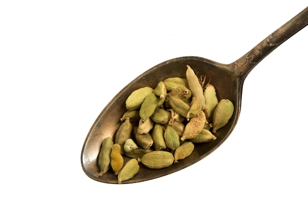 Dry fennel seeds in a spoon on a white background.