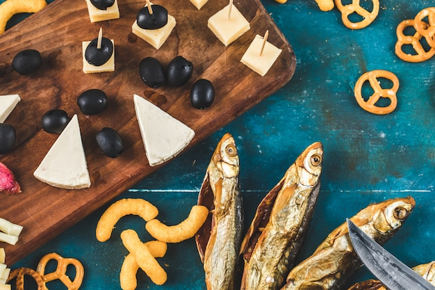 Dry fish snack with cheese, olive and crackers