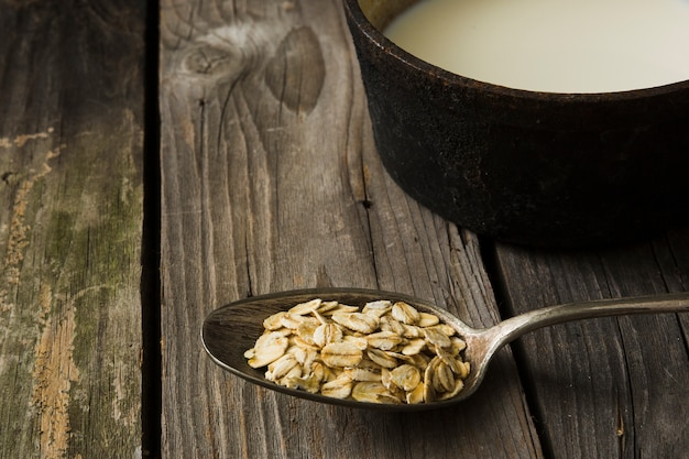 Dry flakes of oat in the rustic spoon and milk on wooden background