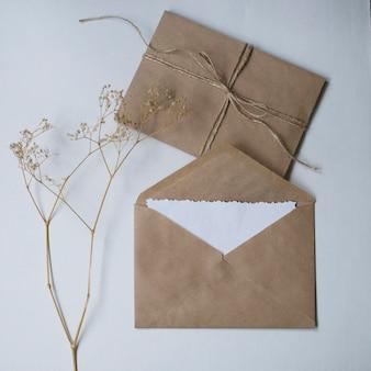 흰색 배경에 마른 꽃과 크래프트 봉투.