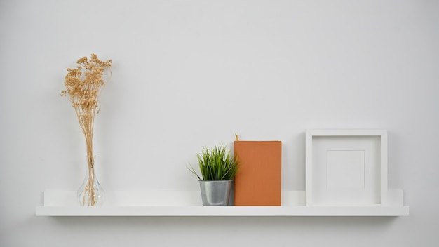 Dry flower, plant, notebook and photo frame on shelves.