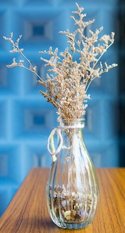 Dry flower vase on wooden table with  blue background