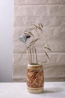 Сухие цветы и ветки ветвятся в коричневой керамической вазе на белом мраморном столе с серой стеной позади. скопируйте пространство.