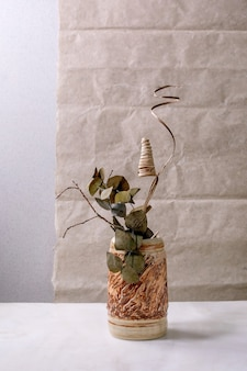 Dry flowers, eucalyptus and twigs branch in brown ceramic vase on white marble table with gray wall behind. c