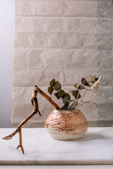 Dry flowers, eucalyptus and twigs branch in brown ceramic vase on white marble table with gray wall behind. copy space.