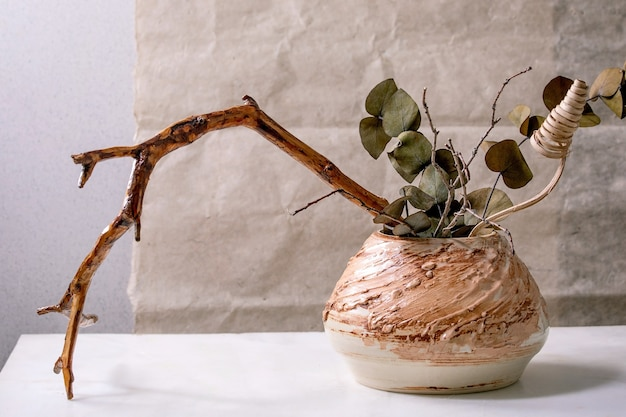 Dry flowers, eucalyptus and twigs branch in brown ceramic vase on white marble table with gray wall behind.