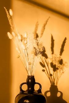 日没時の花瓶に乾いた花、固い影。