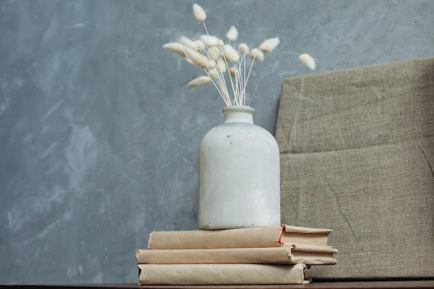 リネンの絵の背景に古い花瓶に花を乾燥させます。テキストのためのスペース。