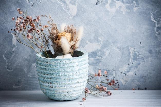 Сухие цветы в синем горшке на белом деревянном столе.