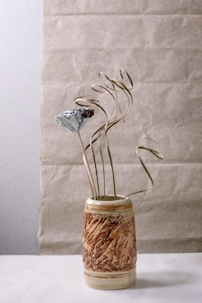 Dry flowers and twigs branch in brown ceramic vase on white marble table with gray wall behind. copy space.