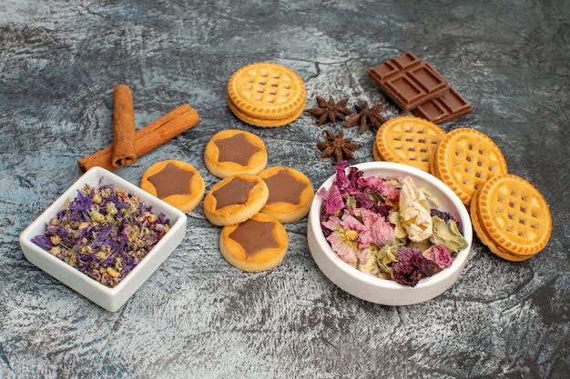Fiori secchi su ciotole bianche con biscotti e barrette di cioccolato su fondo grigio