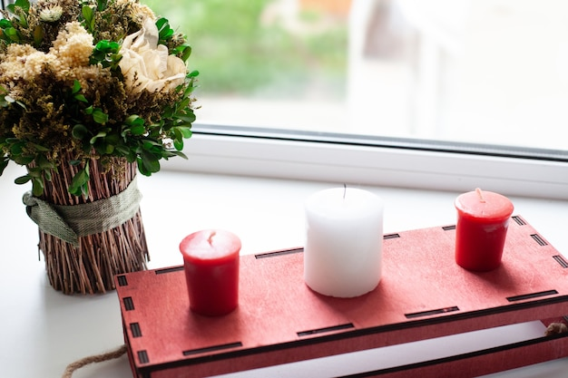 Dry flowers and white, red candles, a red wooden box on the window.