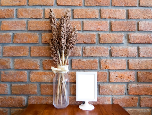 Dry flowers on wooden table with red brick wall and copy space